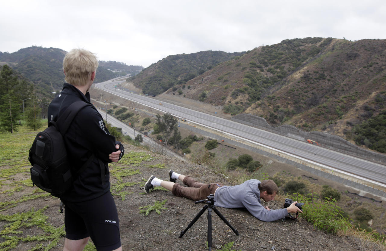 Ian Kalmbaugh, lying on the ground, photographs Interstate 405 as a 10-mile stretch of the freeway is shut down to demolish the Mulholland Drive bridge in Los Angeles, Saturday, July 16, 2011. Traffic in the Los Angeles area is so far moving smoothly, several hours after authorities shut down the 10-mile (16-kilometer) stretch of one of the busiest U.S. freeways for a massive 53-hour construction project. (AP Photo/Jae C. Hong)