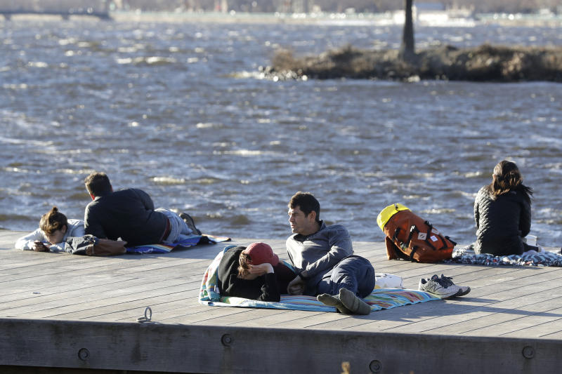 Phil Taneyhill, center right, and his wife Elisa, center left, both of Boston, sit on a dock in the Charles River Esplanade park, in Boston, Sunday, Jan. 12, 2020, while enjoying unseasonably warm weather. Temperatures climbed into the low 70s in many places in the state Sunday. (AP Photo/Steven Senne)