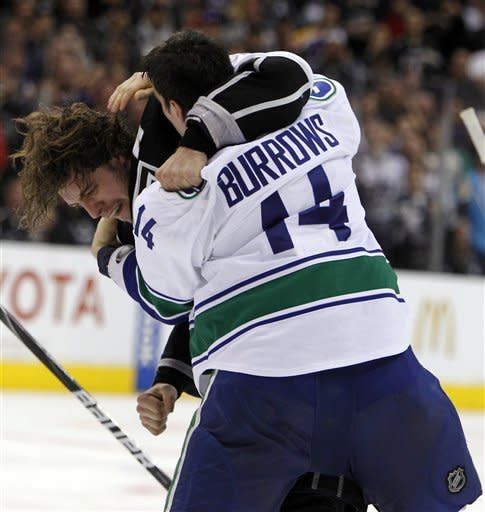 Los Angeles Kings center Anze Kopitar, left, of Yugoslavia fights with Vancouver Canucks right wing Alex Burrows (14) during the second period of Game 3 in a first-round NHL Stanley Cup playoff series in Los Angeles, Sunday, April 15, 2012. (AP Photo/Alex Gallardo)