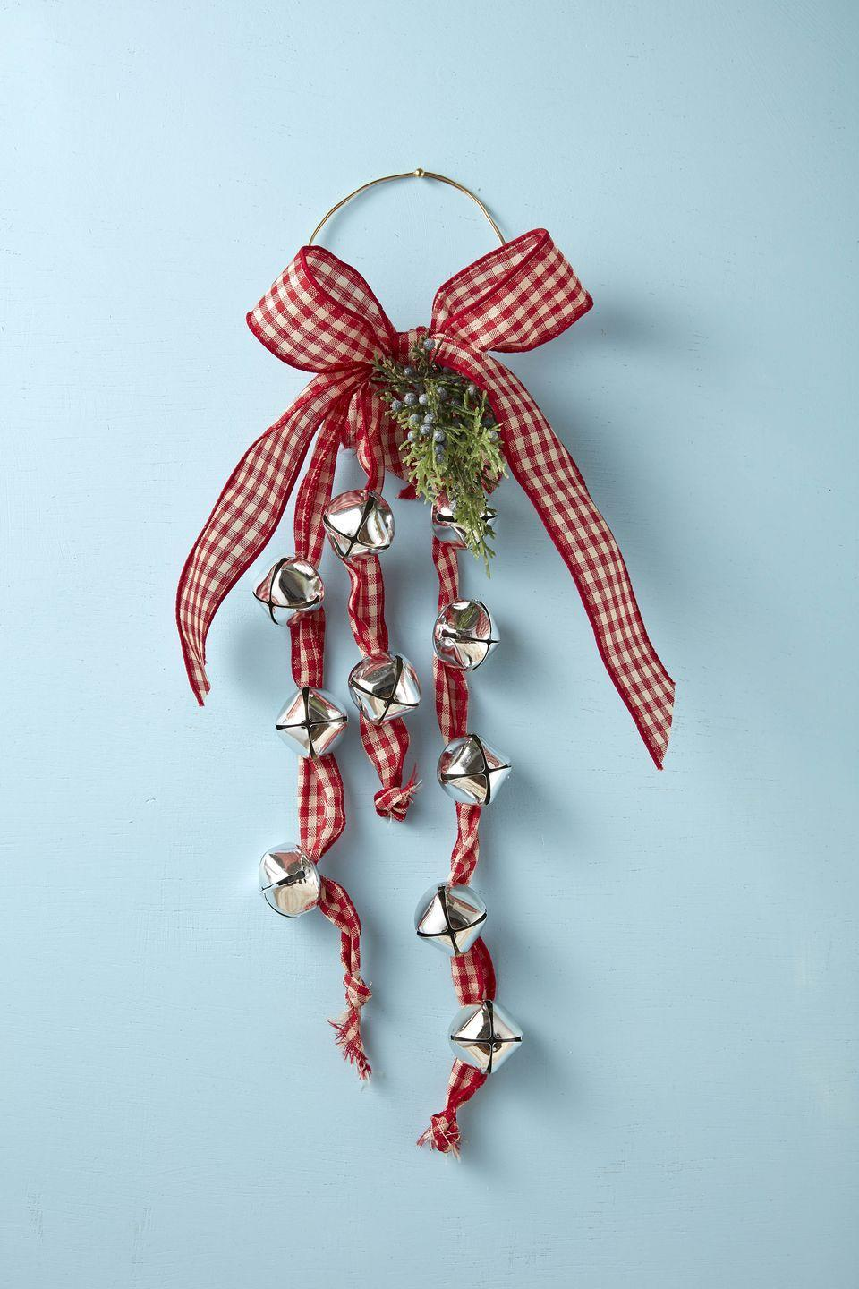 "<p>Kids will love helping you make this sweet holiday noise maker. Have them thread the bells on the ribbon while you tie the bow. Hang on the front door, above the mantel, or at the end of a bed. </p><p><strong>To make: </strong>Thread large jingle bells onto three lengths of ribbon; knot one end of the ribbon. Tie the unknotted end around a small wreath form or a length of wire shaped into a circle. Wire together a small bunch of seasonal greenery; attach to the wreath or circle form. Tie an oversized bow and hot glue to the wire just above the greenery. </p><p><a class=""link rapid-noclick-resp"" href=""https://www.amazon.com/Jingle-Christmas-Festival-Decoration-Silver/dp/B074W73J88/ref=sr_1_2_sspa?tag=syn-yahoo-20&ascsubtag=%5Bartid%7C10050.g.5030%5Bsrc%7Cyahoo-us"" rel=""nofollow noopener"" target=""_blank"" data-ylk=""slk:SHOP LARGE JINGLE BELLS"">SHOP LARGE JINGLE BELLS</a></p>"