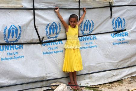 A Syrian refugee girl stands outside a tent as she poses at a refugee camp in Zahrani town, southern Lebanon June 13, 2018. REUTERS/Ali Hashisho