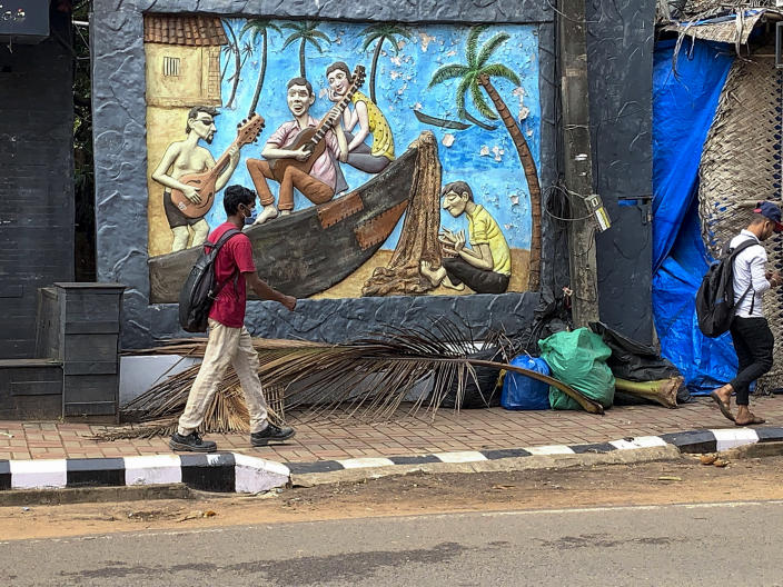 A man wearing a mask walks past a mural near the Candolim beach on the Arabian Sea coast in Goa, India, Dec.11, 2020. The unspoken fear of the coronavirus is sapping Goa's vibrant beach shacks and noisy bars of their lifeblood. The coastal state usually comes alive in December and January, its tourism-led economy booming with foreign travelers and chartered flights bringing in hordes of vacationers. Goans are mourning the loss of their livelihoods and possibly their way of life to the pandemic and travel restrictions. (AP Photo/Vineeta Deepak)