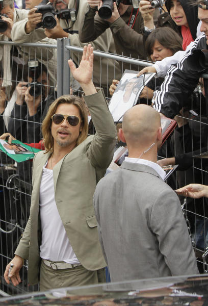 Actor Brad Pitt waves as he arrives at a photo call for Killing Them Softly at the 65th international film festival, in Cannes, southern France, Tuesday, May 22, 2012. (AP Photo/Francois Mori)