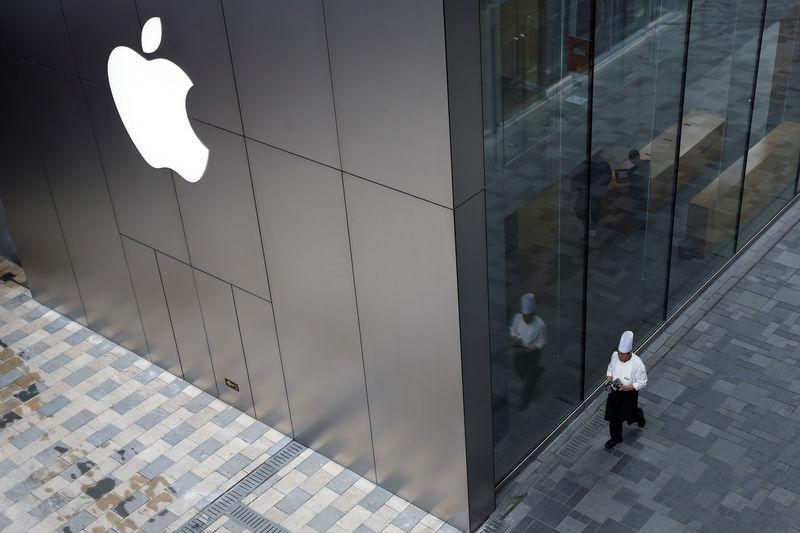 FILE PHOTO: Chef walks past an Apple store in Beijing