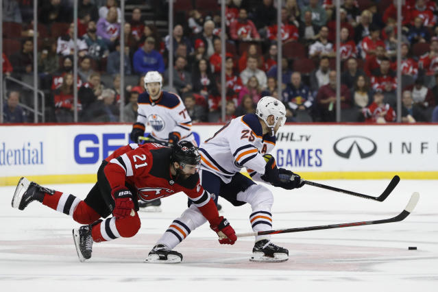New Jersey Devils center Kyle Palmieri (21) trips while trying to defend against Edmonton Oilers defenseman Darnell Nurse (25) during the first period of an NHL hockey game Thursday, Oct. 10, 2019, in Newark, N.J. (AP Photo/Kathy Willens)