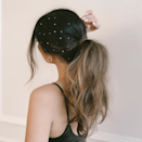 """This style can be more ethereal or more glam depending on how many crystals you use and how messy your pony is. To create this look, hairstylist Justine Marjan used <a href=""""https://www.instagram.com/tv/B53CsGaBLMl/"""" rel=""""nofollow noopener"""" target=""""_blank"""" data-ylk=""""slk:eyelash glue and tweezers"""" class=""""link rapid-noclick-resp"""">eyelash glue and tweezers</a> to add flat-backed rhinestones to the pony."""