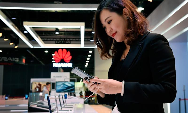 A woman looking at a Huawei smartphone Huawei sign in background at CES in Las Vegas.