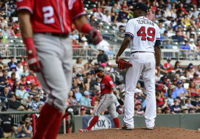 Atlanta Braves pitcher Julio Teheran (49) waits for his next pitch after walking Washington Nationals' Adam Eaton (2) with the bases loaded allowing Wilmer Difo, center, to take third base and Juan Soto to score during the fourth inning of a baseball game Saturday, Sept. 15, 2018, in Atlanta. (AP Photo/John Amis)