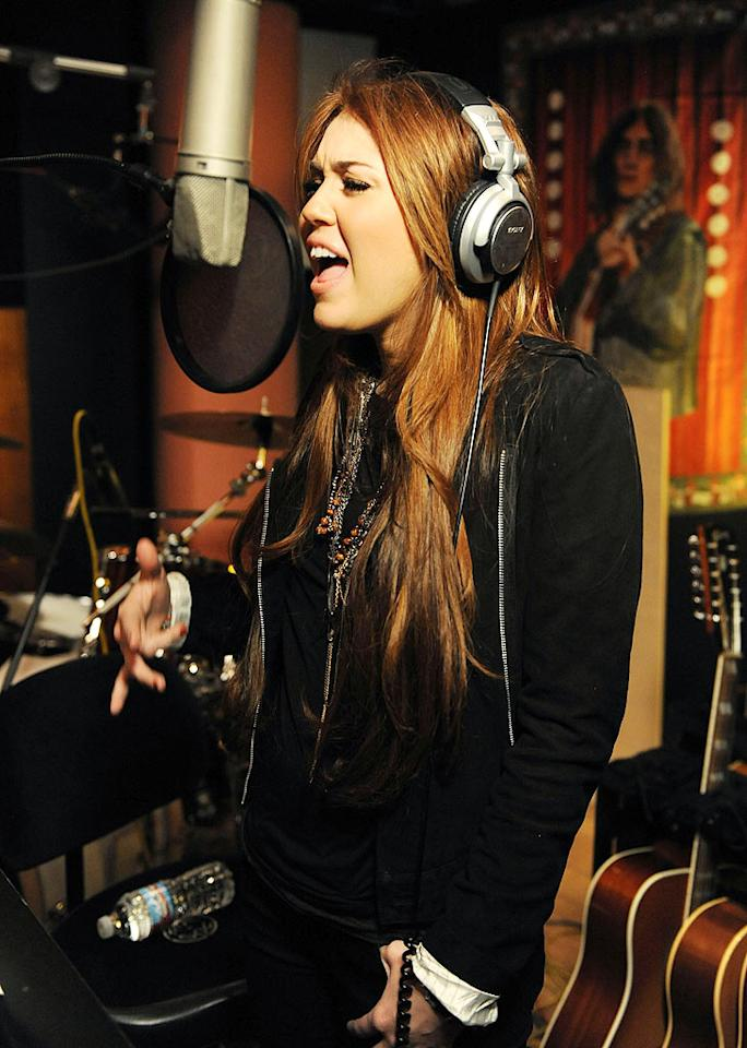 "Teen queen Miley Cyrus belted out her part in a recording booth. Kevin Mazur/<a href=""http://www.wireimage.com"" target=""new"">WireImage.com</a> - February 1, 2010"