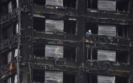 FILE PHOTO:An official works in the burnt out remains of the Grenfell apartment tower in North Kensington, London, Britain