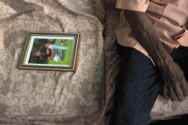A Guatemalan relative of Gilmar Castillo Morales -- one of the 72 illegal migrants killed in the Mexican state of Tanaulipas -- sits beside his picture during a 2010 interview in Agua Caliente, on the outskirts of Guatemala City