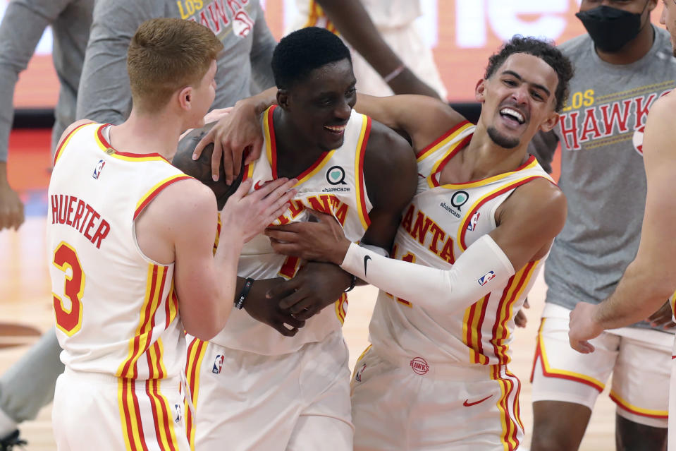 Atlanta Hawks' Tony Snell, center, is congratulated by Kevin Huerter (3) and Trae Young after his basket at the buzzer that gave the team a 121-120 win over the Toronto Raptors in an NBA basketball game Thursday, March 11, 2021, in Tampa, Fla. (AP Photo/Mike Carlson)