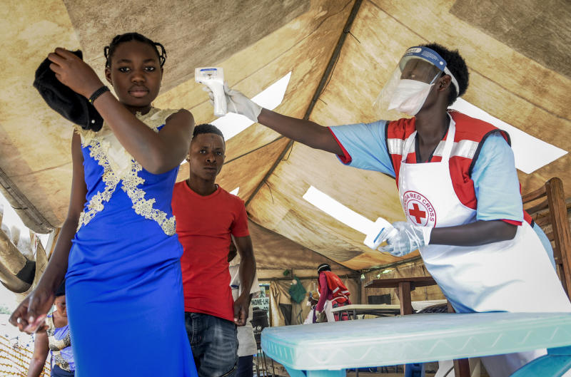 People coming from Congo have their temperature measured to screen for symptoms of Ebola, at the Mpondwe border crossing with Congo, in western Uganda Friday, June 14, 2019. In Uganda, health workers had long prepared in case the Ebola virus got past the screening conducted at border posts with Congo and earlier this week it did, when a family exposed to Ebola while visiting Congo returned home on an unguarded footpath. (AP Photo/Ronald Kabuubi)