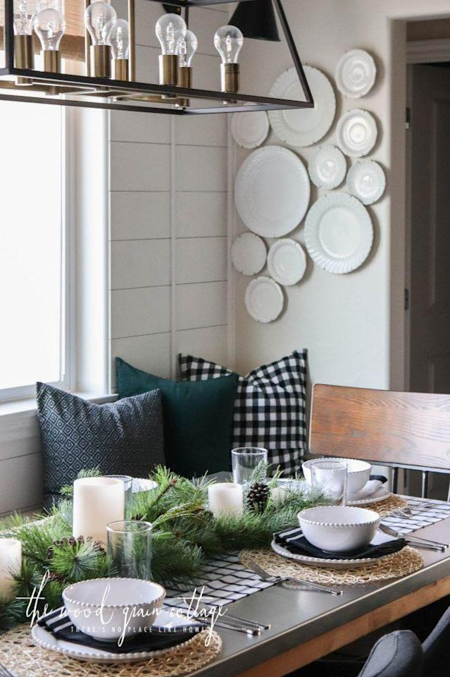 """<p>A strip of black and white window pane fabric straight from the store serves as the foundation for this cute Christmas brunch setting. No sewing required!</p><p><strong>Get the tutorial at <a href=""""https://www.thewoodgraincottage.com/2017/12/04/christmas-table-setting-breakfast-nook/"""" rel=""""nofollow noopener"""" target=""""_blank"""" data-ylk=""""slk:The Wood Grain Cottage"""" class=""""link rapid-noclick-resp"""">The Wood Grain Cottage</a>.</strong></p><p><a href=""""https://www.ikea.com/us/en/catalog/products/00342876/"""" rel=""""nofollow noopener"""" target=""""_blank"""" data-ylk=""""slk:SHOP WOVEN PLACEMATS"""" class=""""link rapid-noclick-resp"""">SHOP WOVEN PLACEMATS</a></p>"""