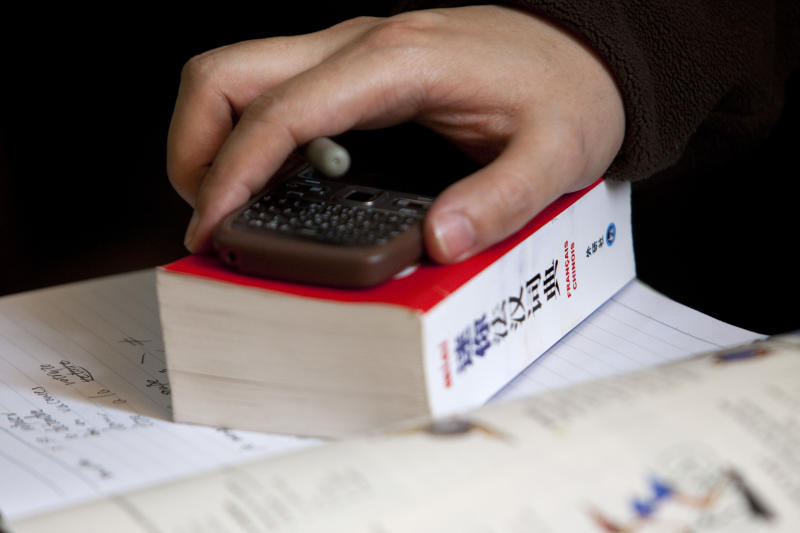 In this Sunday, Feb. 26, 2012 photo, a student rests his hand on a Chinese-French dictionary during a French course of Alliance Francaise, an organization that promotes French language and culture, in Tianjin, China. Thousands of people in China are trying to write their own ticket out of the country - in French. Chinese desperate to emigrate have discovered a backdoor into Canada that involves applying for entry into the country's francophone province of Quebec - as long as you have a good working knowledge of the local lingo. (AP Photo/Alexander F. Yuan)