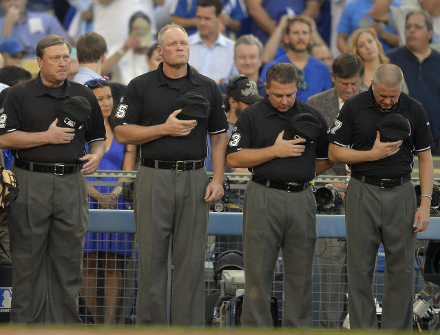 Umpires pause for a moment of silence for umpire Wally Bell before Game 4 of the National League baseball championship series between the St. Louis Cardinals and the Los Angeles Dodgers Tuesday, Oct. 15, 2013, in Los Angeles. Bell, a veteran of 21 big league seasons, died Monday, Oct. 14, 2013, of an apparent heart attack at 48.(AP Photo/Mark J. Terrill)