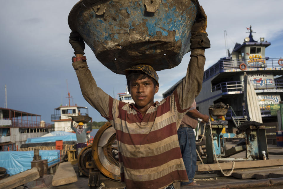 Michael Urquilla carries scrap metals for recycling to a cargo ship, at the Masusa port in Iquitos, Peru, Friday, March 19, 2021. It's been almost a year that dozens who died of COVID-19 were secretly buried in a field in Iquitos, a city in Loreto state in the heart of the Peruvian Amazon. Nobody is able to explain why the clandestine burials were held. (AP Photo/Rodrigo Abd)