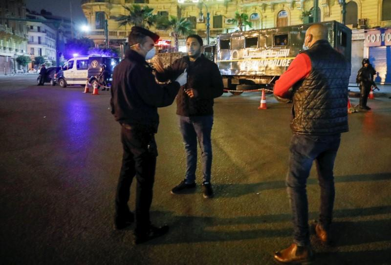 A police officer debriefs a man, near Tahrir square during the first day of a two-weeks night-time curfew which was ordered by the Egyptian Prime Minister Mostafa Madbouly to contain the spread of the coronavirus disease (COVID-19), in Cairo