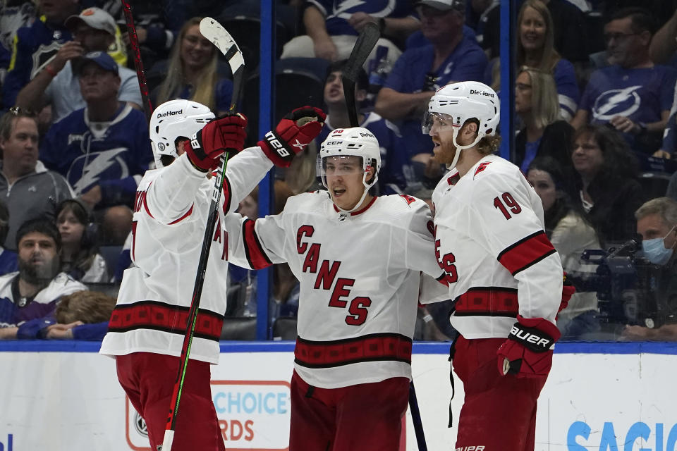 Carolina Hurricanes defenseman Dougie Hamilton (19) celebrates with teammates, including right wing Sebastian Aho (20) after scoring against the Tampa Bay Lightning during the second period in Game 4 of an NHL hockey Stanley Cup second-round playoff series Saturday, June 5, 2021, in Tampa, Fla. (AP Photo/Chris O'Meara)