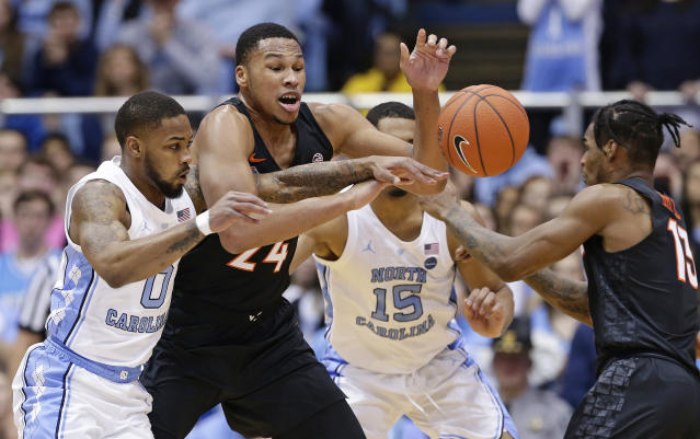 North Carolina's Seventh Woods (0) reaches for the ball with Virginia Tech's Kerry Blackshear Jr. (24) and Ahmed Hill (13) during the first half of an NCAA college basketball game in Chapel Hill, N.C., Monday, Jan. 21, 2019. (AP Photo/Gerry Broome)