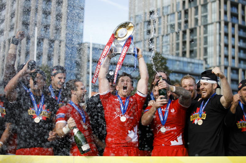 Toronto Wolfpack captain Josh McCrone raises the trophy alongside teammates after defeating the Featherstone Rovers in the Million Pound Game in a Betfred Championship rugby play-off game in Toronto, Saturday, Oct. 5, 2019. (Cole Burston/The Canadian Press via AP)