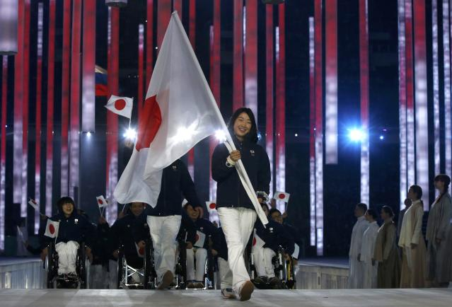 Japan's flag-bearer Shoko Ota (C), leads his country's contingent during the opening ceremony of the 2014 Paralympic Winter Games in Sochi, March 7, 2014. REUTERS/Alexander Demianchuk (RUSSIA - Tags: OLYMPICS SPORT)