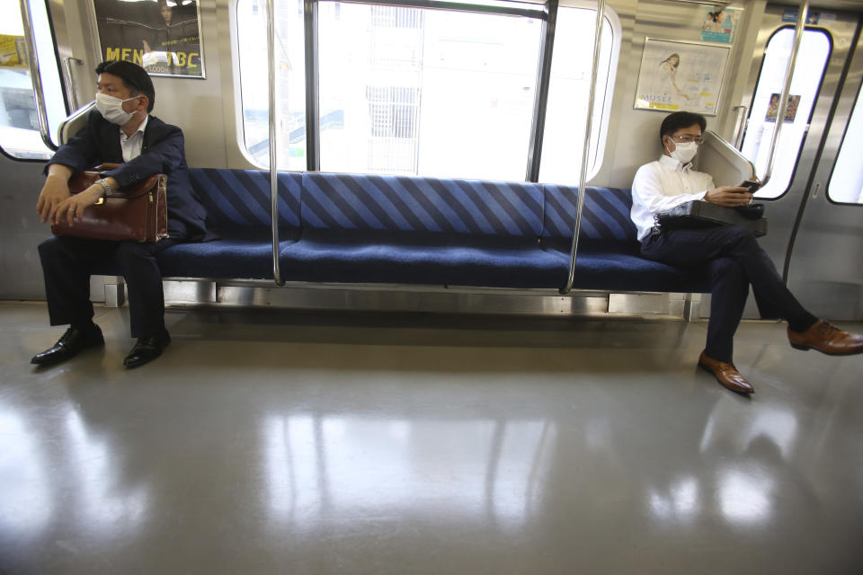 People wearing face masks to protect against the spread of the new coronavirus keep social distancing in a train in Yokohama, near Tokyo, Thursday May 28, 2020. Japanese Prime Minister Shinzo Abe lifted a coronavirus state of emergency on Monday, ending the restrictions nationwide as businesses begin to reopen. (AP Photo/Koji Sasahara)