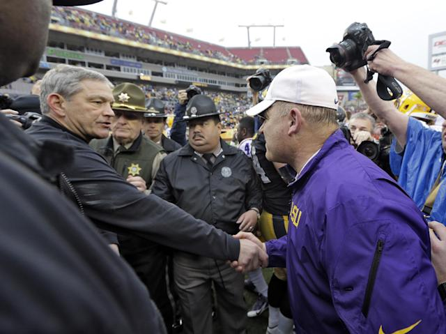 LSU head coach Les Miles, right, shakes hands with Iowa head coach Kirk Ferentz after LSU defeated Iowa 21-14 in the Outback Bowl NCAA college football game Wednesday, Jan. 1, 2014, in Tampa, Fla. (AP Photo/Chris O'Meara)