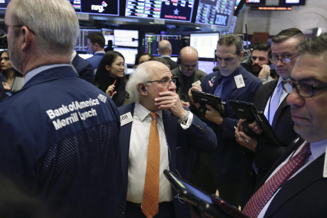 A wave of selling hit U.S. equity funds at the end of March. Trader Peter Tuchman, center, stands on the floor of the New York Stock Exchange. (AP Photo/Richard Drew)