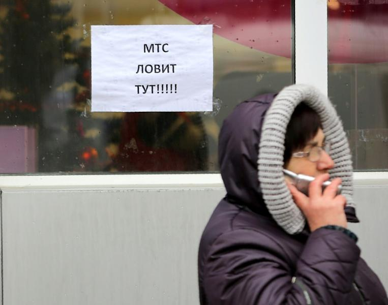 """A caller tries to catch a signal from cell phone towers by a sign reading """"MTS is available here"""" in one of the few places available for mobile connection provided by Vodafone Ukraine (former MTS) in Donetsk"""