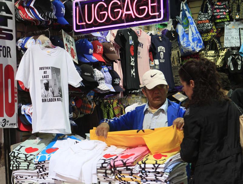 In this photo taken Tuesday, May 10, 2011, a vendor sells T-shirts in New York's Times Square. After President Obama announced the death of Osama bin Laden, vendors rushed to print up T-shirts bearing his name. But now the merchandise mania may be tapering off.  (AP Photo/Mary Altaffer)