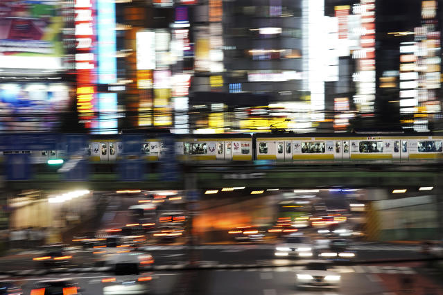 In this July 30, 2019, photo, a train packed with commuters travels through the Shinjuku district of Tokyo during evening rush hours. Tokyo has one of the most advanced public transport systems in the world, but with less than one year to go before the city hosts the 2020 Olympic Games, local governments, companies and commuters are bracing for unprecedented strain the events could put on rail transit and highways. (AP Photo/Jae C. Hong)