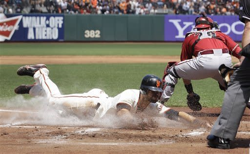San Francisco Giants' Angel Pagan, left, scores on a single by Hector Sanchez past Arizona Diamondbacks catcher Miguel Montero during the first inning of a baseball game in San Francisco, Monday, May 28, 2012. (AP Photo/Jeff Chiu)