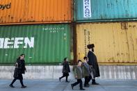 FILE - In this Tuesday, March 30, 2021 file photo, members of the Orthodox Jewish community walk past shipping containers in the South Williamsburg neighborhood of Brooklyn, New York. A comprehensive new survey of Jewish Americans finds them increasingly worried about antisemitism and sharply divided about the importance of religious observance in their lives. The wide-ranging survey, released on Tuesday, May 11, 2021, was conducted by the Pew Research Center. (AP Photo/Wong Maye-E)