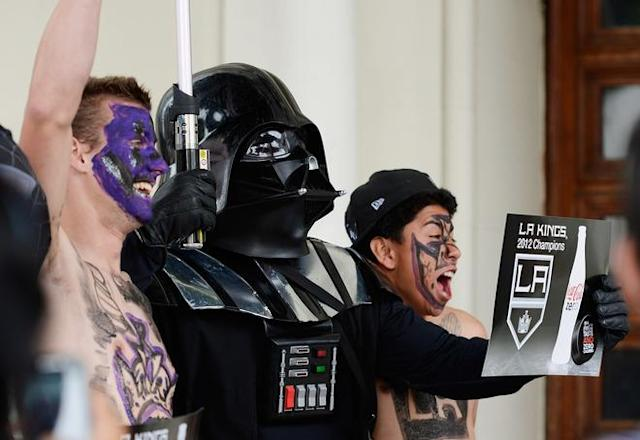 LOS ANGELES, CA - JUNE 14: Corey Brankin (L) and Johnny Castellanos (R) from Lancaster, California, get their picture taken with Star Wars character Darth Vader during the Stanley Cup victory parade on June 14, 2012 in Los Angeles, California. The Kings are celebrating their first NHL Championship in the team's 45-year-old franchise history. (Photo by Kevork Djansezian/Getty Images)
