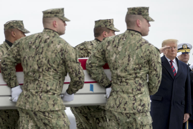 President Donald Trump salutes as a U.S. Navy carry team moves a transfer case containing the remains of Scott A. Wirtz, Saturday, Jan. 19, 2019, at Dover Air Force Base, Del. According to the Department of Defense, Wirtz, a civilian and former Navy SEAL from St. Louis, Mo., was killed Jan. 16, 2019, in a suicide bomb attack in Manbij, Syria. (AP Photo/Andrew Harnik)