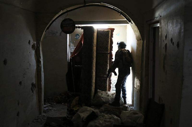 A member of the Iraqi forces, consisting of the Iraqi federal police and the elite Rapid Response Division, secures a building as troops push into the Old City in Mosul on March 19, 2017 (AFP Photo/AHMAD AL-RUBAYE)