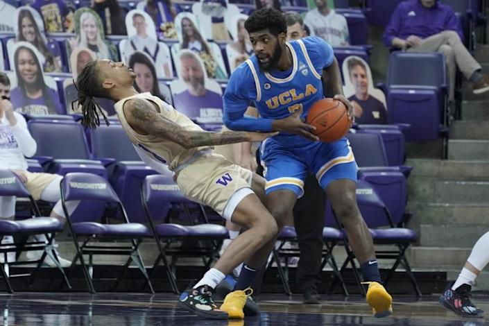 CORRECTS WASHINGTON PLAYER TO HAMEIR WRIGHT, INSTEAD OF NATE ROBERTS - UCLA forward Cody Riley, right, collides with Washington forward Hameir Wright, left, during the first half of an NCAA college basketball game, Saturday, Feb. 13, 2021, in Seattle. (AP Photo/Ted S. Warren)