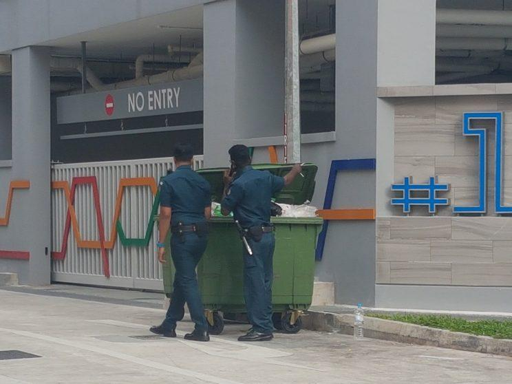Auxiliary officers going through a dumpster as they look for contraband cigarettes at Lorong 6 Geylang. (Yahoo Singapore photo: Safhras Khan)