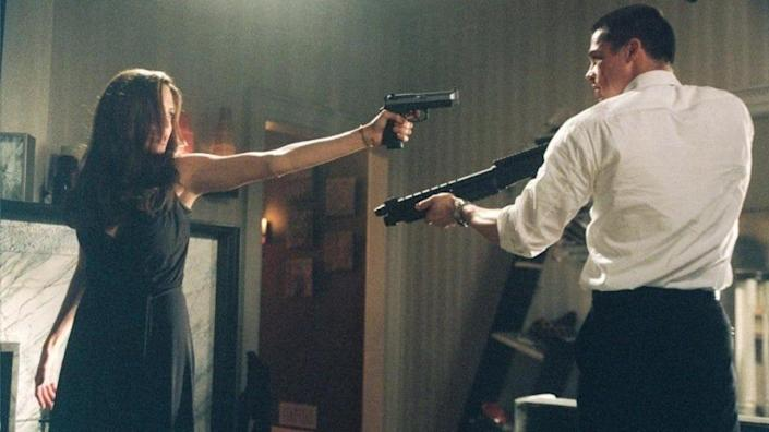 """Angelina Jolie and Brad Pitt pointing guns at one another in the famous fight scene from the movie """"Mr & Mrs Smith"""""""