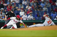 Philadelphia Phillies third baseman Freddy Galvis, left, tags out Baltimore Orioles' John Means at third after Means tried to advance on a passed ball during the seventh inning of an interleague baseball game, Monday, Sept. 20, 2021, in Philadelphia. (AP Photo/Matt Slocum)
