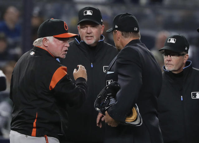 Baltimore Orioles manager Buck Showalter, left, argues with umpires about a call on a rundown involving New York Yankees' Giancarlo Stanton and Gary Sanchez during the sixth inning of a baseball game Friday, April 6, 2018, in New York. While Showalter argued they were both out on the play, the umpires ruled Stanton out at home and Sanchez safe at third base. (AP Photo/Julie Jacobson)