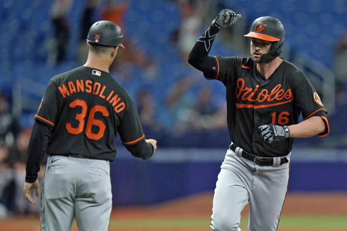 Baltimore Orioles' Trey Mancini (16) celebrates ith third base coach Tony Mansolino (36) after Mancini hit a two-run home run off Tampa Bay Rays starting pitcher Ryan Yarbrough during the third inning of a baseball game Friday, June 11, 2021, in St. Petersburg, Fla. (AP Photo/Chris O'Meara)