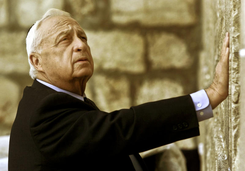 """FILE - In this Wednesday Feb. 7, 2001 file photo, Ariel Sharon, then Israel's Prime Minister-elect, looks up as he touches Judaism holiest site, the Western Wall, in Jerusalem. The son of former Israeli Prime Minister Ariel Sharon says his father has died on Saturday, Jan. 11, 2014. The 85-year-old Sharon had been in a coma since a debilitating stroke eight years ago. His son Gilad Sharon said: """"He has gone. He went when he decided to go."""" (AP Photo/David Guttenfelder, File)"""