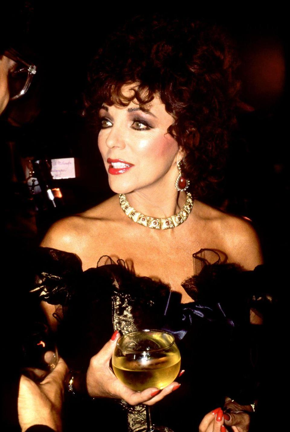 <p>Collins partied the night away at her friend and fellow Dame's house in a ruffled black satin gown, accessorised with gold, diamonds and rubies. </p>