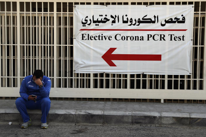 "A man checks his mobile phone as he sits near the emergency entrance of the coronavirus testing center at the Rafik Hariri University Hospital in Beirut, Lebanon, Monday, Jan. 11, 2021. Lebanon's caretaker prime minister said Monday the country has entered a ""very critical zone"" in the battle against coronavirus as his government mulls tightening nationwide lockdown announced last week. (AP Photo/Bilal Hussein)"