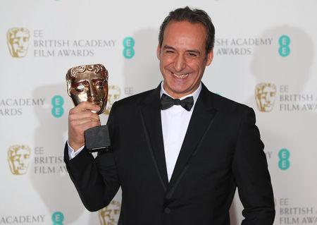 Alexandre Desplat holds his award for Original Music at the British Academy of Film and Television Awards (BAFTA) at the Royal Albert Hall in London, Britain, February 18, 2018. REUTERS/Hannah McKay