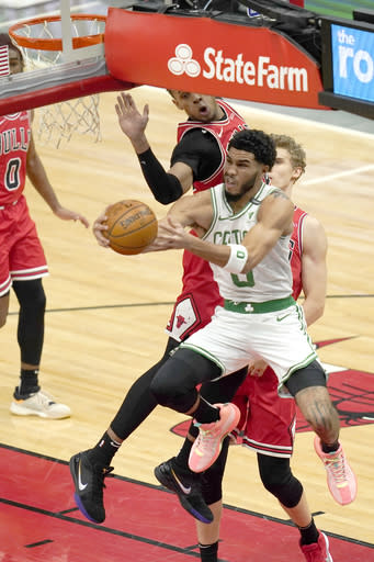 Boston Celtics' Jayson Tatum (0) drives for a reverse layup past Chicago Bulls' Lauri Markkanen during the first half of an NBA basketball game, Monday, Jan. 25, 2021, in Chicago. (AP Photo/Charles Rex Arbogast)