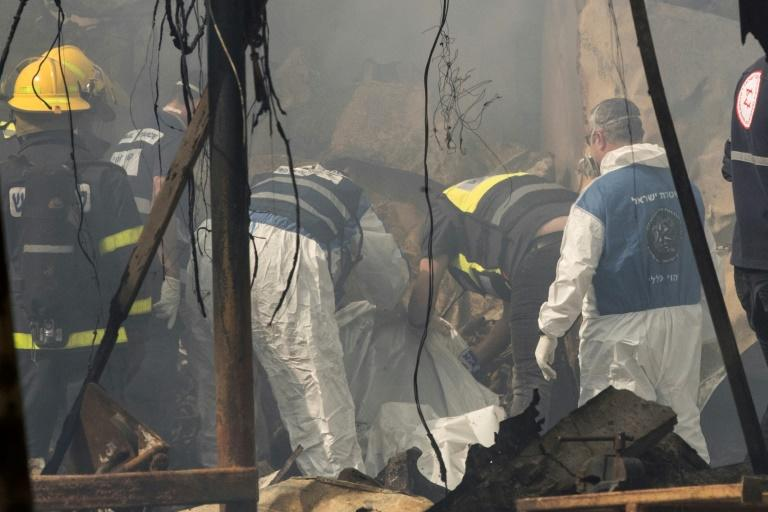 Rescue workers inspect a body after a fireworks warehouse blaze in the Israeli village of Porat on March 14, 2017