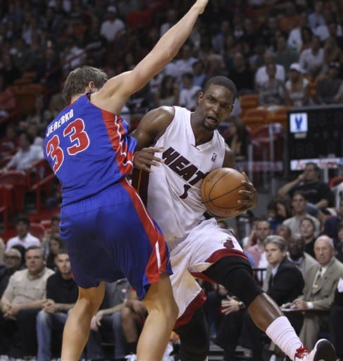 Miami Heat's Chris Bosh (1) goes around Detroit Pistons' Jonas Jerebko (33) for a two point shot during the first half of a NBA basketball game in Miami, Sunday, April 8, 2012.(AP Photo/J Pat Carter)